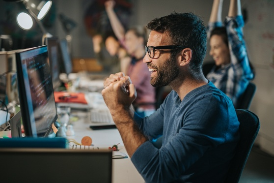 Millennial man wearing glasses looking at computer excited 2.2